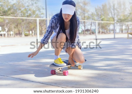 Young asian women play surf skate board at park skate ramp outdoors on morning. Happy women play surfskate board at park . Sport activity lifestyle concept