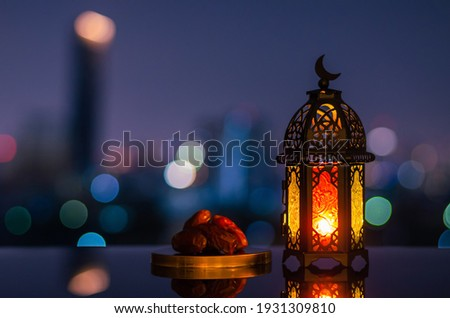 Lantern that have moon symbol on top and small plate of dates fruit with night sky and city bokeh light background for the Muslim feast of the holy month of Ramadan Kareem. Royalty-Free Stock Photo #1931309810