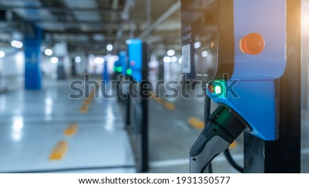 Blur photo of electric car charging station for charge EV battery. Plug for vehicle with electric engine. EV charger. Clean energy. Charging point at car parking lot. Future transport technology. Royalty-Free Stock Photo #1931350577