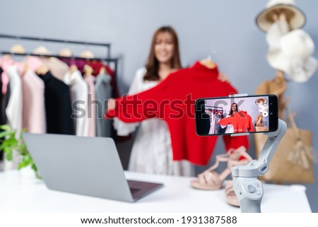 young woman selling clothes online by smartphone live streaming, business online e-commerce at home Royalty-Free Stock Photo #1931387588