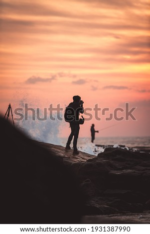 Photographer standing on the rock faces taking photos of the beautiful sunrise
