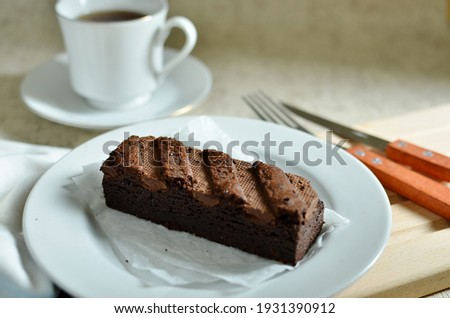 chocolate brownies dessert on white plate and a cup of tea