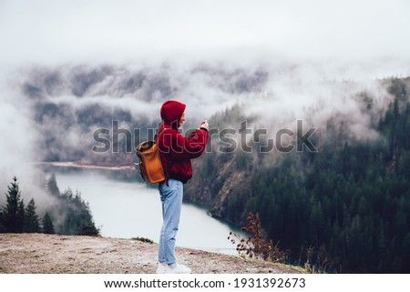 Side view of anonymous person looking at green forest located near calm water while spending time in cold day outside