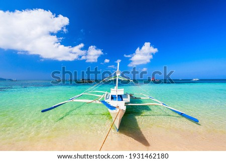 Traditional filipino boat at the idyllic white sand beach at Boracay island in Philiphines Royalty-Free Stock Photo #1931462180
