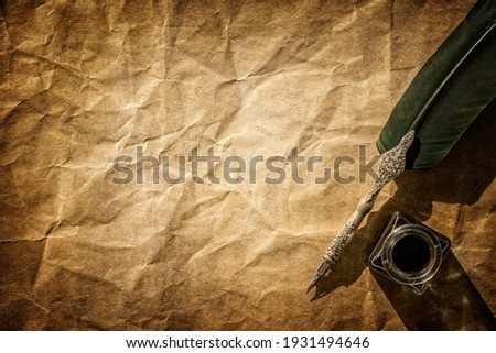 Quill pen and ink well resting on blank parchment paper background with copy space for message Royalty-Free Stock Photo #1931494646