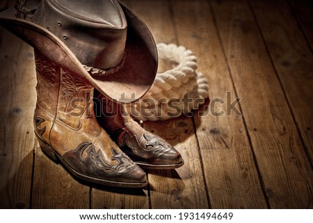Country music festival live concert or rodeo with cowboy hat and boots background Royalty-Free Stock Photo #1931494649