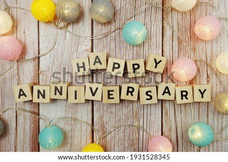 Happy Anniversary alphabet letter with LED cotton balls on wooden background Royalty-Free Stock Photo #1931528345