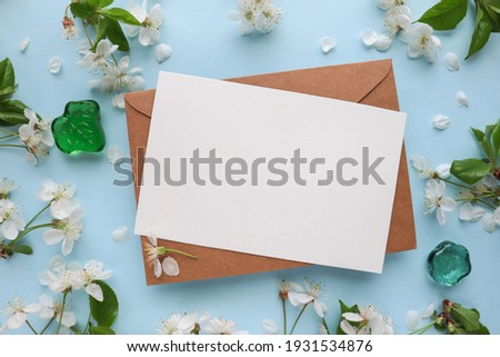 postcard mockup. floral frame of spring flowers, envelope and white blank for text Royalty-Free Stock Photo #1931534876