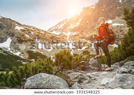 Woman hiker, hiking backpacker traveler camper walking on the top of mountain in sunny day under sun light. Beautiful mountain landscape view. Royalty-Free Stock Photo #1931548325