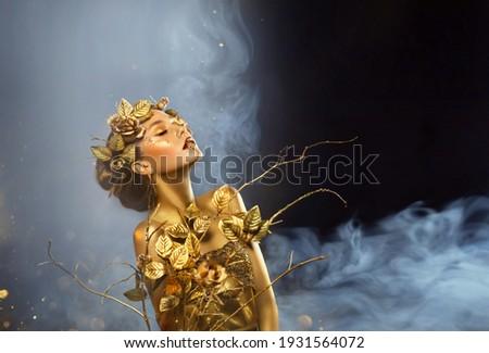 Fantasy portrait of woman, golden skin body. Girl goddess in wreath gold roses dress. Beautiful face steel glitter art makeup. Art photo black background white blue smoke. Girl princess Fashion model