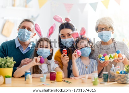 Mother, grandparents and children are painting eggs. Happy family are preparing for Easter. Cute little girls wearing bunny ears. Royalty-Free Stock Photo #1931574815