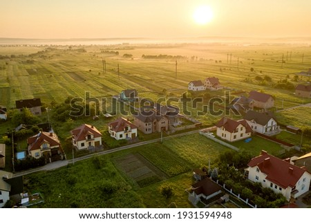 Aerial view of rural residential area with private homes between green fields at sunrise. Royalty-Free Stock Photo #1931594948