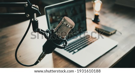 Home studio podcast interior. Microphone, laptop and on air lamp on the table, close-up