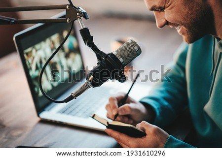 Cheerful host streaming his audio podcast using microphone and laptop at his small broadcast studio