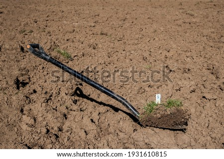 A valuable shovel. The demand for land is increasing worldwide and the purchase price for arable land has increased by an average of 187 percent over the past few years.  Royalty-Free Stock Photo #1931610815