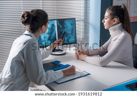 Doctor explaining a x-ray to the patient and pointing at the computer screen, the woman is wearing a cervical collar Royalty-Free Stock Photo #1931619812