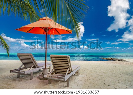 Beautiful tropical island scenery, two sun beds, loungers, umbrella under palm tree. White sand, sea view with horizon, idyllic blue sky, calmness and relaxation. Inspirational beach resort hotel Royalty-Free Stock Photo #1931633657