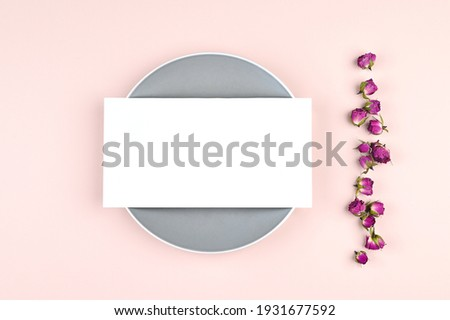 Horizontal blank white card on circle background and pastel paper, dried rose buds on background. Empty space. Styled stock photo, web banner. Flat lay, top view. High quality photo
