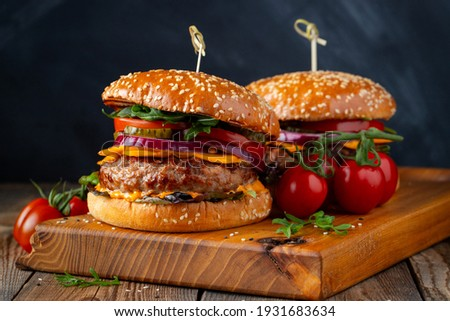 Two delicious homemade burgers of beef, cheese and vegetables on an old wooden table. Fat unhealthy food close-up