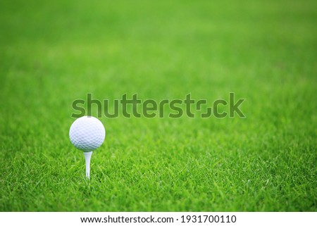 Golf ball on tee on green grass of golf course background, backgrounds for banner foth copy space for text Royalty-Free Stock Photo #1931700110