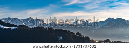 Panorama view of the snowy mountains between Switzerland, Liechtenstein and Austria. in foreground Austrian Alp with meadows and huts in the middle of the woods and in Background mountain range peaks Royalty-Free Stock Photo #1931707682