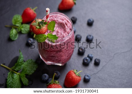 Delicious strawberry, mulberry and blueberry smoothie garnished with fresh berries and mint in glass. soft focus. beautiful appetizer pink raspberries, well being and weight loss concept. Royalty-Free Stock Photo #1931730041
