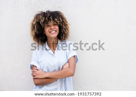 Horizontal portrait smiling young african american teen girl with curly hair and arms crossed by white background
