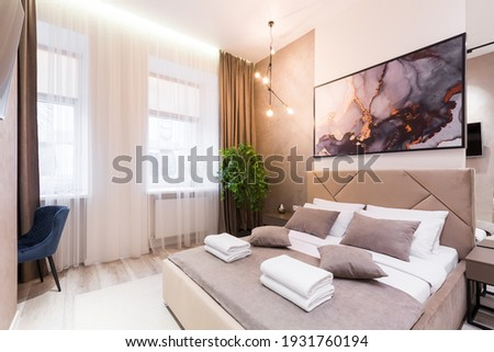 Interior photography, modern bedroom, with large stylish bed, modern design, in beige