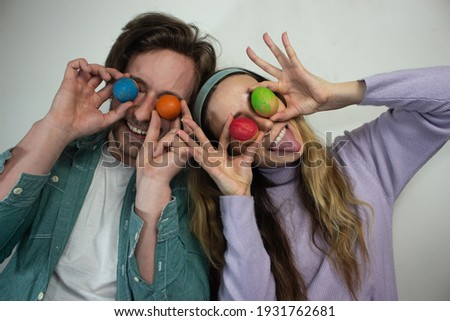 Picture of young couple having fun with painted Easter eggs at home. Concept couple Happy Easter. Young couple with colorful outfit holding painted eggs doing funny faces.