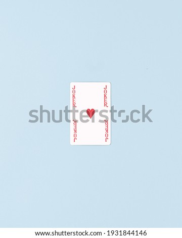 Jocker card with one red heart in the middle. Minimal flat lay composition. Pastel blue background.