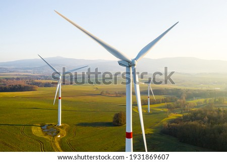 Panoramic view of wind farm or wind park, with high wind turbines for generation electricity with copy space. Green energy concept. Royalty-Free Stock Photo #1931869607