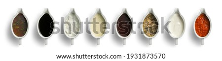Barbecue, soy, ranch, cheese, ketchup, mushroom sauce, sour cream and adjika. Set of several different oriental sauces in beautiful ceramic saucepans on a white background. Royalty-Free Stock Photo #1931873570
