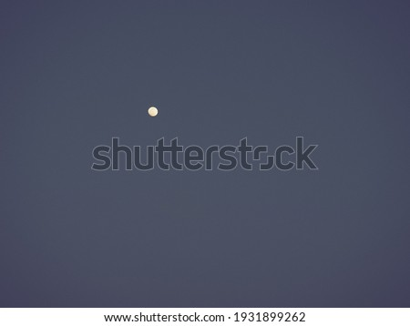 Moon in the night blue sky. White point in the sky. Dark vignetting around the edges of the image