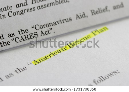 Closeup of the documents of both the Cares Act (Coronavirus Aid, Relief, and Economic Security Act) and the American Rescue Plan Act (ARPA) of 2021. Royalty-Free Stock Photo #1931908358