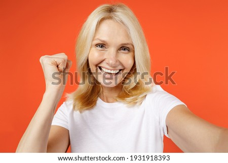 Close up of joyful elderly gray-haired blonde woman lady 40s 50s years old in white casual t-shirt doing selfie shot on mobile phone doing winner gesture isolated on orange background studio portrait