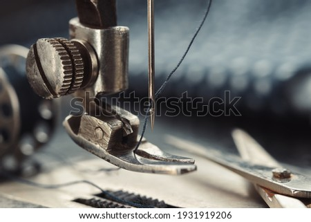Close up of sewing needle. Tailoring scissors on working part of antique sewing machine. Royalty-Free Stock Photo #1931919206