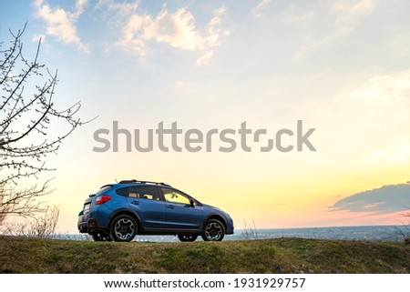 Landscape with blue off road car at sunset, Traveling by auto, adventure in wildlife, expedition or extreme travel on a SUV automobile. Offroad 4x4 vehicle in field at sunrise. Royalty-Free Stock Photo #1931929757
