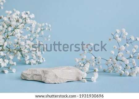 A minimalistic scene of a lying stone with flowers on a light blue background. Catwalk for the presentation of products and cosmetics. Showcase with a stage for natural products. Royalty-Free Stock Photo #1931930696