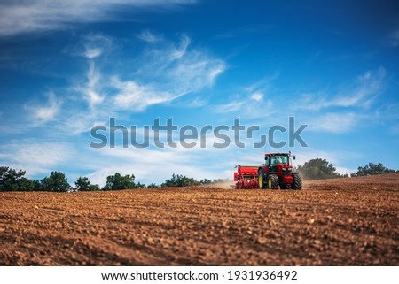 Farmer in tractor preparing farmland with seedbed for the next year Royalty-Free Stock Photo #1931936492
