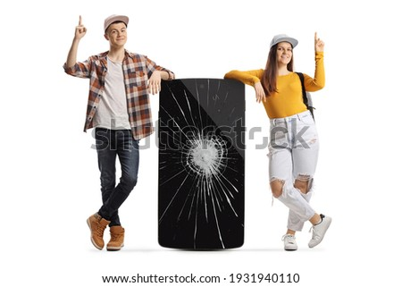 Young male and female leaning on a phone with a broken screen and pointing up isolated on white background