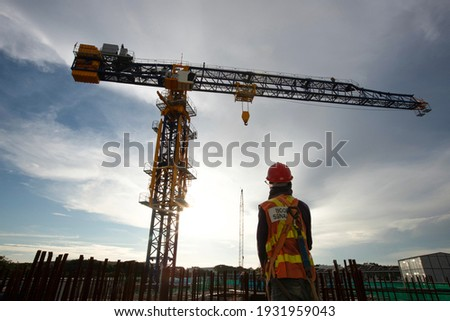 Worker, Rigger signal with crane at construction site  Royalty-Free Stock Photo #1931959043