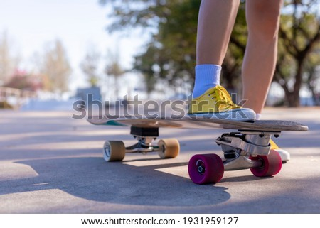 Close-up Asian women surf skate or skateboard outdoors on beautiful morning. Happy young women play surf skate at ramp park on morning time. Close up Asian women leg wear sneaker play surf skate