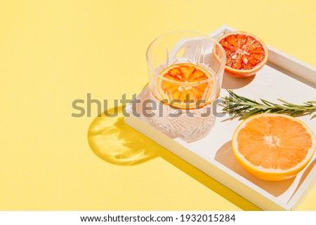 Half of grapefruit and bloody orange, rosemary on a white wooden tray and glass with water on bright yellow background. Summer refreshment concept. Sunlit flat lay. Minimal style. Top view. Royalty-Free Stock Photo #1932015284