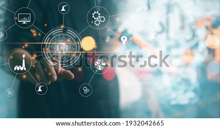 Mechanical engineering pointing on virtual screen working with blur Industrial robotic welding and robot gripping working on smart factory background. industry 4.0 and technology Ai. Royalty-Free Stock Photo #1932042665