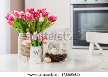 A bouquet of tulips, Easter bunnies and eggs with a golden pattern on the table. In the background is a white Scandinavian-style kitchen. Beautiful greeting card. The minimal concept. Royalty-Free Stock Photo #1932056816