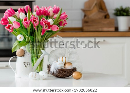 A bouquet of tulips, Easter bunnies and eggs with a golden pattern on the table. In the background is a white Scandinavian-style kitchen. Beautiful greeting card. The minimal concept. Royalty-Free Stock Photo #1932056822