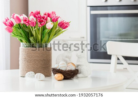A bouquet of tulips, Easter bunnies and eggs with a golden pattern on the table. In the background is a white Scandinavian-style kitchen. Beautiful greeting card. The minimal concept. Royalty-Free Stock Photo #1932057176