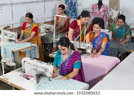 Senior inspector explaining women textile worker sewing garment on production line Royalty-Free Stock Photo #1932080033