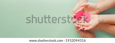 Adult and child holding kidney shaped paper on textured blue background, world kidney day, National Organ Donor Day, charity donation concept Royalty-Free Stock Photo #1932094316