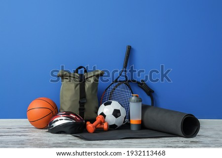 Set of sport equipment on floor near color wall Royalty-Free Stock Photo #1932113468